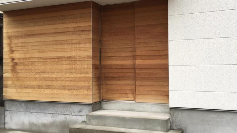 木製の玄関ドアと外壁の塗装はがれ